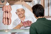 Happy mature male butcher showing packed sausages to customer at butchery