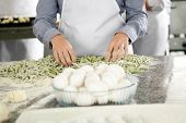 Midsection of female chef standing at counter with spaghetti pasta and egg bowl in commercial kitchen