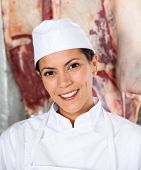 Closeup portrait of confident female butcher smiling in butchery