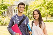Smiling friends student standing with shoulder bag holding book in park at school