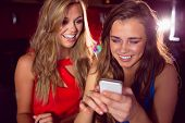 Pretty friends looking at smartphone together at the nightclub