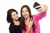image of two women taking cell phone  - Two girls friends taking selfie with smartphone - JPG