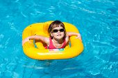 Cute Girl Swims In A Pool In A Yellow Life Preserver