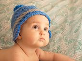 Portrait of an infant in a knitted cap.
