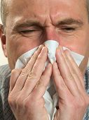 Man Blows His Nose In A Handkerchief