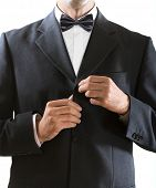 hands of the man who in a black tuxedo clasps a jacket button