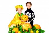 Cute boy and a girl wearing halloween costumes posing with pumpkin. Halloween. Isolated over white.