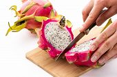 Hands Of A Chef Cutting A Dragonfruit In Half