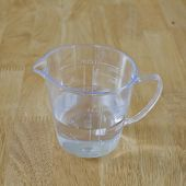 Warm Water In Measuring Cup On A Wood Background