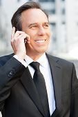 stock photo of toothless smile  - Confident senior man in formalwear talking on the mobile phone and smiling while standing outdoors - JPG
