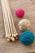 Three Colorful Balls And Wooden Needles Lying On Beige Knitted Plaid