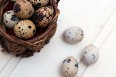 Quail Eggs In A Wicker Basket On A Wooden Background