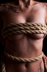 stock photo of sadism  - beautiful naked female body is bounded with a rope - JPG