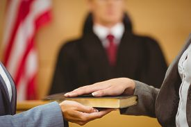 stock photo of frown  - Witness swearing on the bible telling the truth in the court room - JPG