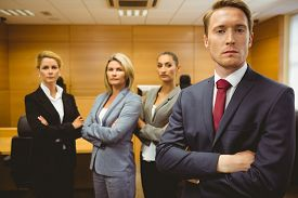 picture of half-dressed  - Serious lawyer standing with arms crossed in the court room - JPG