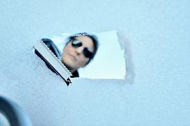 foto of scrape  - Woman with sunglasses scraping ice from a windshield - JPG