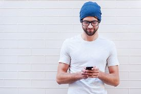 picture of adults only  - Handsome young man in eyeglasses holding mobile phone and looking at it while standing against brick wall - JPG