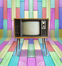 stock photo of tv sets  - Old vintage TV television on colorful wooden wall background - JPG