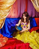 foto of harem  - Young oriental beauty sitting in the tent and plays a pleasant melody on the tabla - JPG
