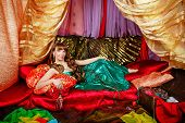 picture of harem  - Sexy oriental beauty is in the tent on the pillows - JPG