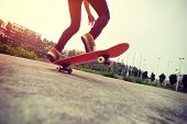 picture of skateboard  - young woman skateboarder practice skateboarding trick ollie outdoor - JPG