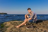 stock photo of nearly nude  - Attractive young fashion sexy man sitting on a rock near the sea water with shoes beside him - JPG