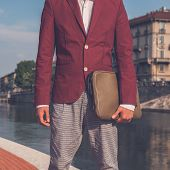 picture of blazer  - Detail of a young handsome Asian model dressed in red blazer posing by an urban artificial basin - JPG