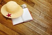 stock photo of panama hat  - Straw hat with book and red starfish on shabby wooden background - JPG