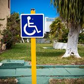 picture of handicap  - Blue handicapped sign with wheelchair at tropical street - JPG