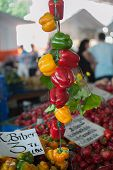pic of yellow-pepper  - A group of green yellow and red bell peppers hanged at market place with a sign saying Red Bell Peppers are 3 TL  per kilogram - JPG