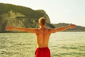 picture of sportive  - Sportive man on the sea with outstretched arms  - JPG