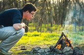 pic of bonfire  - Man and bonfire in spring forest - JPG