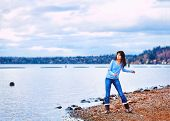 foto of biracial  - Young biracial teen girl in blue shirt and jeans along rocky lake shore throwing rocks into the water on cloudy overcast day - JPG