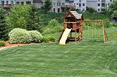 stock photo of swingset  - Back Yard Wooden Swing Set on Green Lawn - JPG