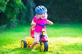 foto of little young child children girl toddler  - Children riding a bike - JPG