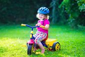 image of little young child children girl toddler  - Children riding a bike - JPG