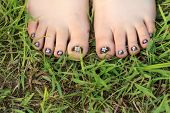 stock photo of toe nail  - Little girl toes with childish handmade floral nail art - JPG