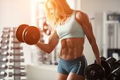 stock photo of woman bikini  - Strong woman bodybuilder with white hair and tanned body pumps up the muscles lifting dumbbells in the gym - JPG