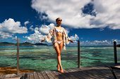 picture of jetties  - Woman with sarong on a tropical beach jetty at at Seychelles - JPG