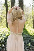 image of evening gown  - Back potrait of beautiful blond curly woman wearing evening peach color gown in outdoors - JPG