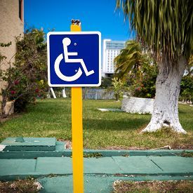 foto of handicapped  - Blue handicapped sign with wheelchair at tropical street - JPG