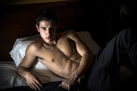 pic of laying-in-bed  - Attractive shirtless athletic young man laying in bed at night, leaning on one elbow, looking at camera