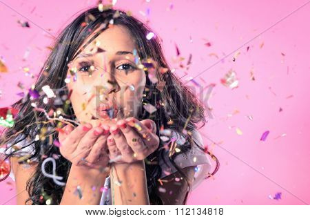 Portrait of beautiful woman blowing confetti in the air, party new years eve celebration on pink bac