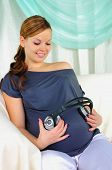 Pregnant woman holding headphones