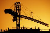 stock photo of construction crane  - a silhouette of a crane and construction workers at sunset - JPG