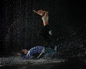 stock photo of dancing rain  - Young couple dancing in water under rain on a black background - JPG