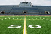 stock photo of football field  - Fifty yard line of American football field with bleachers or stands in the background - JPG