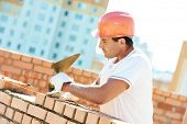 construction worker. mason bricklayer installing red brick with trowel putty knife outdoors poster