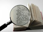stock photo of glossary  - the pocket dictionary consider under a magnifier - JPG