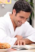 smiling man in robe reading